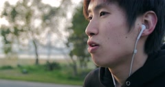 Inspiring young Japanese runner puts in earphones and gets ready to run - stock footage