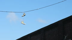 Pair of athletic shoes dangling from a overhead street cable. Stock Footage