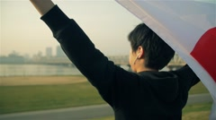 Inspirational shot of young Japanese man holding national flag while training - stock footage