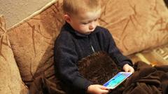 Little boy watching cartoon on a smartphone indoor Stock Footage