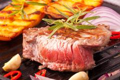 Grilled steak in an iron pan Stock Photos