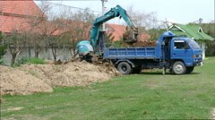 The worker is controlling the excavator of dozer shovel to load the earth Stock Footage