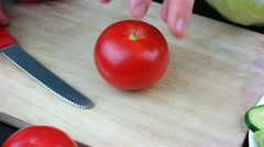 Woman cutting up a tomato with a knife on a wooden board Stock Footage