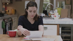 Young adult woman opening bills at home on kitchen table - stock footage