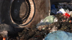 Wheel of a bulldozer driving through the unsorted trash on a landfill site. Stock Footage