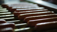 Appetizing hotdog sausages being cooked on grill, snacks at street food festival Stock Footage