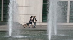 Fountain jets and passersby with suitcase Stock Footage