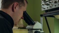 Scientist looking into a microscope - stock footage