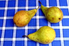 Three Bio pears on a wooden table - stock photo
