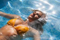 Beautiful young woman floating in sunlit swimming pool wearing yellow bikini Stock Photos
