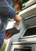 Young woman using cash machine, putting money in purse, low angle view Kuvituskuvat