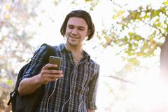 Low angle view of young man holding smartphone looking down smiling Stock Photos