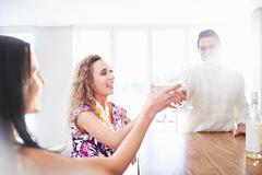 Three young adult friends making a white wine toast at kitchen counter Stock Photos