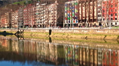 Bilbao northern Spain city colorful apartment flats reflecting in calm river  Stock Footage