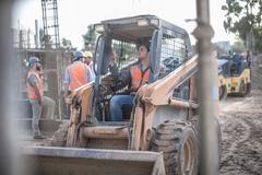 Construction worker driving excavator on construction site - stock photo