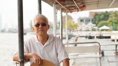 Stock Photo of Senior Asian man riding a ferry boat to cross Chaopraya river in morning sun