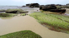 Gentle waves with a Rocky Coastline and Sandy Beach. - stock footage
