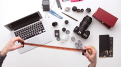 Photographer prepares his desk for work surrounded by a lot of things. Upview Stock Footage