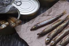 Smoked capelin and conserve tins on wooden background - stock photo