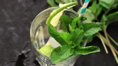 Pouring in glass Iced green tea with lime, lemon and mint on black textured Stock Footage