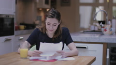 Young adult woman opening bills at home Stock Footage