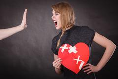 Angry woman holds broken heart screaming at man - stock photo