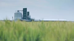 Dolly shot of manufacturing plant,rye or wheat field Arkistovideo