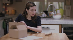Young adult woman packing cupcakes at home in kitchen Stock Footage