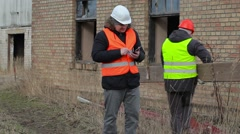 Building inspector with tablet PC and worker with board Stock Footage