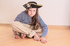 Pretty teen girl sitting on floor in pirate costume - stock photo