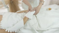 Masseuse put off mitten from right woman hand in beauty saloon. Thermo hand mask Stock Footage
