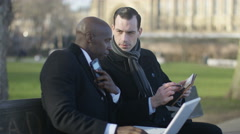 4K Businessmen using technology at outdoor meeting in the city - stock footage