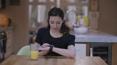 Young adult woman using smart watch at home on kitchen table - stock footage