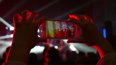 Stock Video Footage of Fan spectator shooting video at a concert via smartphone in flashing lumiere