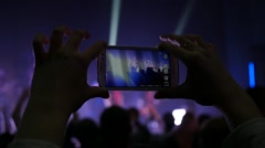 Fan spectator shooting video at a concert via smartphone in flashing lumiere - stock footage