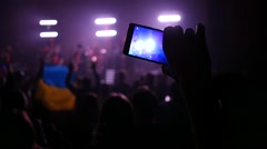 Spectator fan shooting video via smartphone at a music concert lumiere Stock Footage