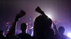 Fan spectator raising hands up in air enjoying music concert in light lumiere - stock footage