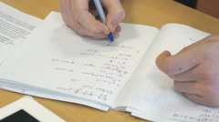 Girl writes in a school mathematics notebook - stock footage
