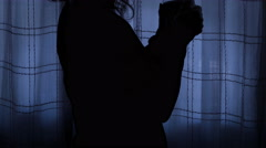 Sad woman closed tent in her room and sips a tea in the darkness Stock Footage