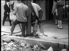 Two workers jackhammering asphalt on city street, 1960s Stock Footage
