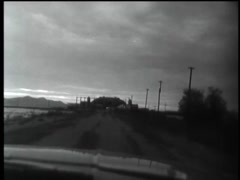 Point of view shot from inside car driving on rural road at dusk, 1960s Stock Footage