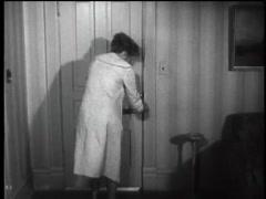 Scared woman locking bedroom door, 1960s Stock Footage