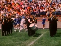 Stock Video Footage of Marching band performing on field at high school football game, 1980s