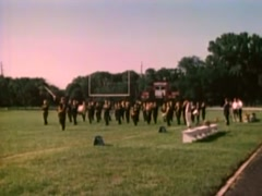 Marching band parading across field as spectators watch from bleachers, 1980s - stock footage