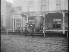 Wide shot of cowboys firing guns outside saloon, 1940s Stock Footage