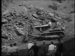 Workers on bulldozer involved in rock excavation, 1950s - stock footage