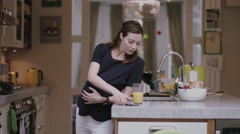 Pregnant woman on phone in kitchen sharing the good news Stock Footage