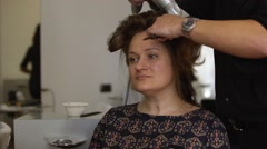 Hairdresser man does hairdo by hair dryer for middle age woman in salon - stock footage