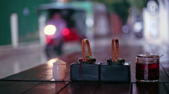 Table sauces and rainy street view from outdoor restaurant, Phnom Penh, Cambodia Stock Footage