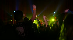 Crowd fan spectators silhouettes rais hands dancing jumping at concert lumiere Stock Footage